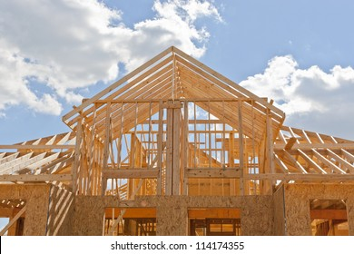 Your dream home. New residential construction house framing against a blue sky.