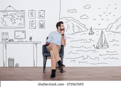 Your dreams can send you far away. Young handsome man keeping hand on chin and looking away while sitting in the chair against illustration of fjord vs. working place