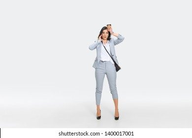 It's your headache now. Young woman in gray suit is getting shocking news from boss or colleagues. Looking numbed while dropping coffee. Concept of office worker's troubles, business, stress.