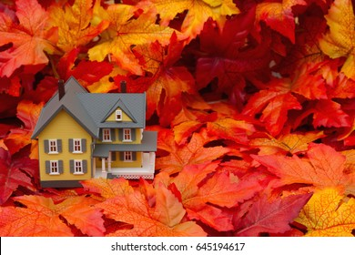 Your home in the fall season, Some fall leaves and yellow and gray house with copy-space for your message