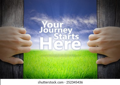 Your Journey Starts Here motivational quotes. Hand opening an old wooden door and found a texts floating over green field and bright blue Sky Sunrise.
