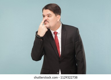 From your lies I see how your nose grows like a pinocchio. indoor studio shot. isolated on light blue background. handsome businessman with black suit, red tie and mustache looking away.