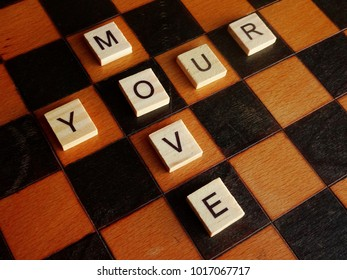 Your move. Wooden letter tiles on old chess board