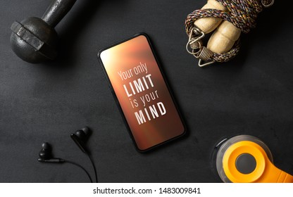 Your only limit is your mind. Inspirational motivational quotes fitness healthy goals with mockup mobile phone on grunge black table with dumbbells, Jump rope, bottle of water. Mock up smartphone.
