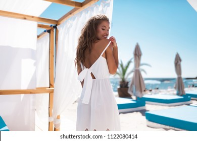Your pretty elegant summer woman posing on the beach club, fluffy hairs white dress,isolated, glamour style and bright colors. Jewelry and accessories.summer style,blue sky
