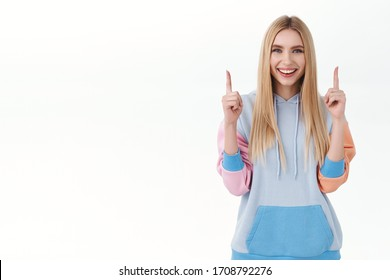 Your promo here. Portrait of attractive, smiling pleased girl with long blond hair, give advice, showing good shopping site, beauty and skincare products advertisement, pointing fingers up