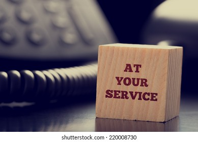At Your Service written on a wooden cube in front of a telephone conceptual of help, client services, assistance, expertise and consultancy.