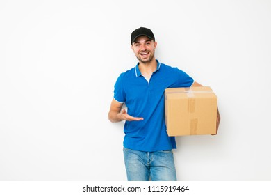 your shipping is here. delivery man in blue shirt standing politely and pointing his cardbox, on white background