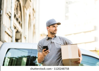 your shipping is here. delivery man in grey shirt with cap standing with his cardboard box on the street using his mobile phone, in front of his car outside on the street