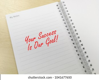 Your Success Is Our Goal! note on notebook background