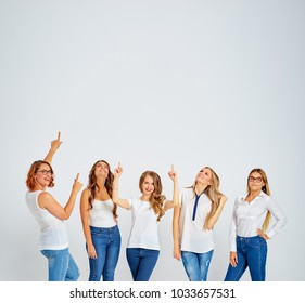 Your tex here. Group of amazed young women looking up and pointing copy space on white background.