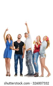 Your tex here. Party and relax. Group of amazed friends with bottles of beer looking up and pointing copy space. Isolated on white.