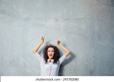 Your text here. Amazed beautiful young woman with curl hair pointing up while standing against grey wall.