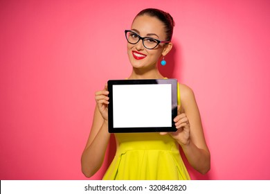 Your text here. Colorful studio portrait of pretty young woman showing screen of tablet computer against pink wall.