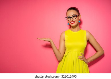 Your text here. Colorful studio portrait of young smiling woman pointing copy space. Pink background.