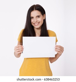 Your text here. Pretty young excited woman holding empty blank board. Studio portrait on white background. Mock up for design