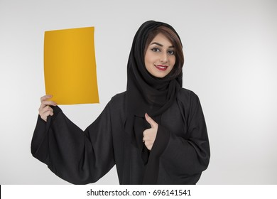 Your text here. Pretty young Arab woman holding empty yellow blank board.  studio portrait with white background.