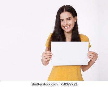 Your text here. Pretty young excited woman holding empty blank board. Studio portrait on white background. Mockup for design