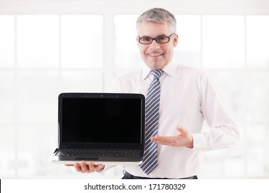 Your text here. Smiling senior man in shirt and tie holding laptop and pointing monitor