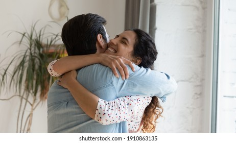 In your warm embraces. Excited wife holding beloved husband tight in arms grateful for support love care. Young couple hug reconciling after family fight or missing each other spending long time apart