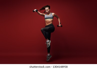 It's Your Workout, Your Time, Your Body, Own It. Sportswoman jumping over red background with dumbbells in her hands