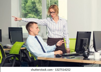 You're fired. A female supervisor shows an employee who wants to dismiss an employee in the direction of exit. Negative conversation of two people in the office near the workplace.