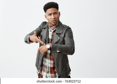 You're late. Portrait of angry beautiful black-skinned mature guy with afro hairstyle in leather jacket pointing on hand watch with unsatisfied expression after friend being late for hour.