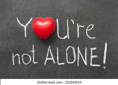 you're not alone exclamation handwritten on blackboard with heart symbol instead of O