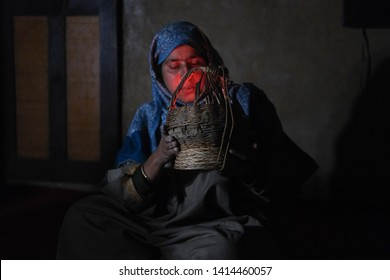 """YOUSMARG, JAMMU AND KASHMIR, INDIA - MAY 2 2019: Kashmiri Kangri (Kanger) heater is being fired up by a housewife. Kangri is in common use within Kashmiris as a """"portable"""" heater during cold days."""