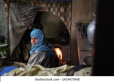 YOUSMARG, JAMMU AND KASHMIR, INDIA - MAY 3 2019: Portrait of Kashmiri Muslim housewife igniting a fireplace to prepare a breakfast for her family