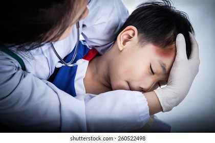 Youth asian (thai) sport boy in blue uniform. Child temple with a bruise, doctor perform first aid by checking. Shoot in studio. Low key lighting picture style