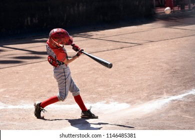 Youth baseball batter hitting ball