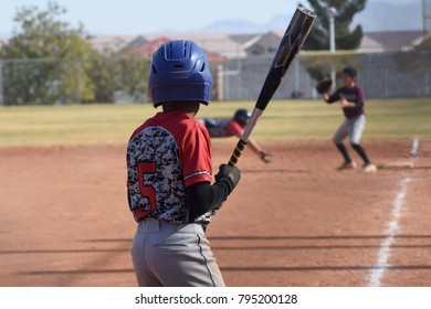 youth baseball batter waits while base runner dives back to first base