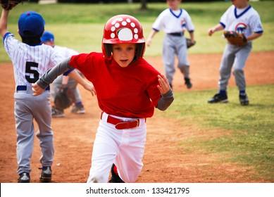 Youth baseball boy running bases.
