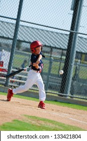 Youth baseball boy swinging the bat.