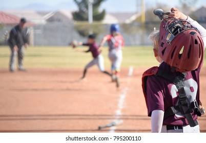 youth  baseball catcher removing helmet and mask to watch the play at first