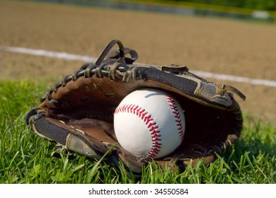 A youth baseball glove and ball laying on the grass next to the infield.