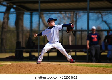 Youth baseball pitcher in wind up wearing white jersey.