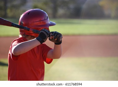 Youth baseball player with bat and batting helmet getting ready to hit