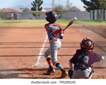 Youth baseball player at bat right after swing, pop fly
