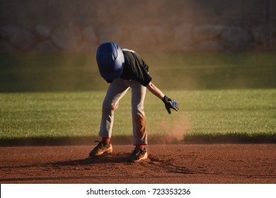 Youth baseball player dusting off infield dirt on second base