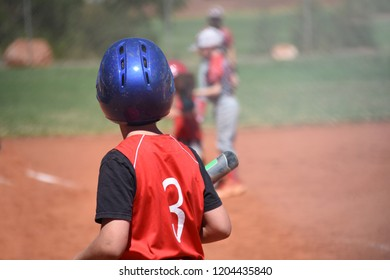 youth baseball player holding bat, waiting to hit
