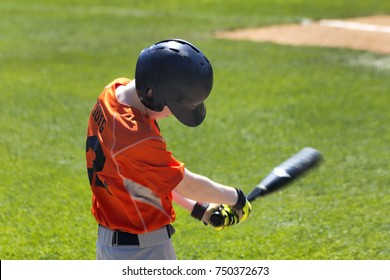 Youth Baseball Player Practicing Swing Before Game