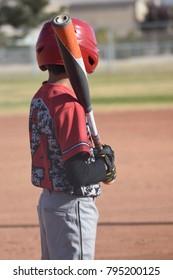 youth baseball player resting bat on shoulder