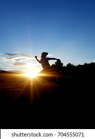youth baseball player silhouette at sunset
