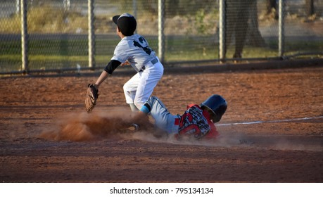 youth baseball player sliding into third base