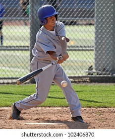 A youth baseball player swings at a ball over the plate.