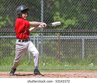 A youth baseball player takes a nice swing at the ball at home plate.