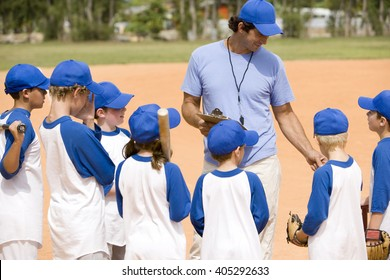 Youth baseball team and coach on pitch