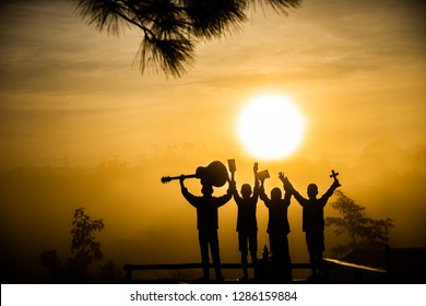 Youth christian group worship God by holding christian cross and guitars with light sun rise background,christian silhouette concept.